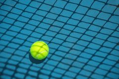 Summer sport concept with tennis ball and net on hard tennis court. Flat lay, top view, copy space stock photography