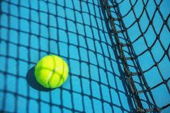 Summer sport concept with tennis ball and net on hard tennis court. Flat lay, top view, copy space royalty free stock images