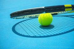 Summer sport concept with tennis ball and racket on blue hard tennis court. Top view, copy space. Blue and yellow royalty free stock photos
