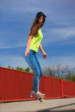 Summer sport. Cool girl skater riding skateboard Royalty Free Stock Photos