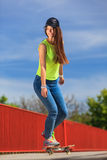 Summer sport. Cool girl skater riding skateboard Stock Photography