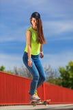 Summer sport. Cool girl skater riding skateboard Stock Photography