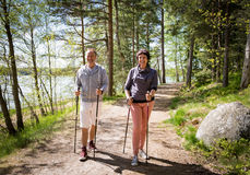 Summer sport in Finland - nordic walking. Man and mature women hiking in green sunny forest. Active people outdoors. Scenic peaceful Finnish summer landscape Stock Photo