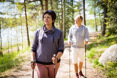 Summer sport in Finland - nordic walking. Man and mature women hiking in green sunny forest. Active people outdoors. Scenic peaceful Finnish summer landscape Stock Images