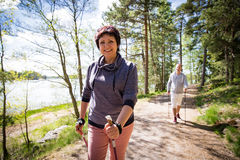 Summer sport in Finland - nordic walking. Man and mature women hiking in green sunny forest. Active people outdoors. Scenic peaceful Finnish summer landscape royalty free stock photography