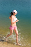 Summer sport fit woman jogging along seashore Royalty Free Stock Photos