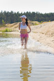Summer sport fit woman jogging along seashore Stock Photography