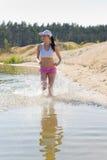 Summer sport fit woman jogging along seashore Stock Photography
