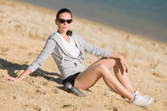 Summer sport fit woman sitting on beach Stock Photography
