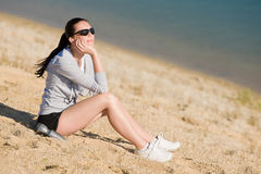 Summer sport fit woman sitting on beach Stock Photo