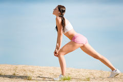 Summer sport fit woman stretching on beach Royalty Free Stock Photos