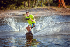 Summer sport wakeboarding. The sportsman slides on the lake`s water on the board Royalty Free Stock Photo