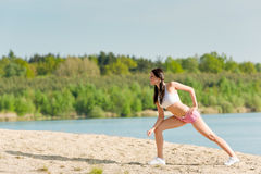 Summer sport woman stretching on beach Stock Photos