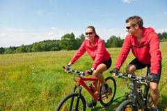 Summer - Sportive couple riding bike in meadow