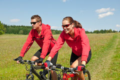 Summer - Sportive couple riding bike in meadow Stock Photography