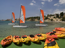 Summer Sports in the Beach. Beautiful mediterranean beach ready for nautical sports in summer, with some catamaran and canoes Stock Image