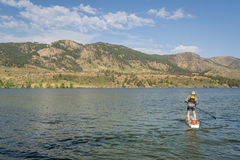 Summer stand up paddleboard on lake in Colorado. Paddling stand up paddleboard on mountain lake in northern Colorado, summer scenery at Horsetooth Reservoir near royalty free stock photography