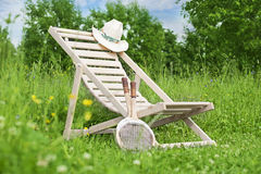 Summer still life with chaise-longue. Chaise-longue with a hat and badminton rackets in the middle of the meadow stock photos