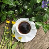 Summer still life in the open air: black coffee and wild flowers on a old gray wooden background royalty free stock photography
