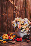 Summer still life. With peaches, raspberries, cherries and flowers on a wooden table Stock Images