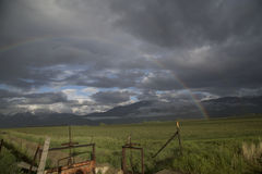 Summer storm with a rainbow over a mountain valley field Royalty Free Stock Photography