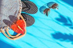 Summer straw bag and singlasses on blue background stock photography