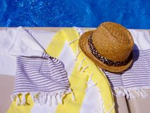 Summer straw hat and cotton towels near the swimming pool. stock photography