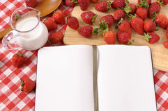 Summer strawberries cream background, blank recipe book, cookbook, copy space. Strawberries and jug of cream with blank recipe book on a chopping board and red Stock Photography