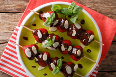 Summer strawberries dessert with chocolate, mint and almonds. Ho. Summer strawberries dessert with chocolate, mint and almonds close-up on a plate. horizontal Stock Photo