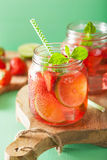 Summer strawberry drink with lime and mint in jars Stock Images