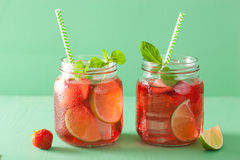 Summer strawberry drink with lime and mint in jars Royalty Free Stock Photo