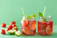 Summer strawberry lemonade with lime and mint in jars Stock Images