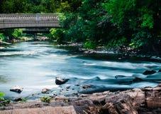 Summer stream flowing under bridge. Beautiful flowing water under a bridge in the heart of Wilmington Delaware royalty free stock photo