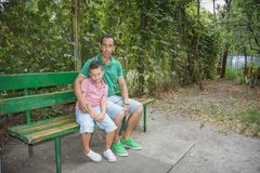Summer in the street on the bench is a son with his father. stock photos