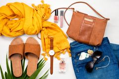 Summer street style. Fashion summer girl clothes set, accessories. Trendy sunglasses, slippers, handbag clutch, watch, jeans, scarf, makeup. Summer lady royalty free stock photo