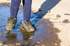 summer stroll kid in shoes in  puddle. Royalty Free Stock Photo