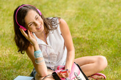 Summer student girl listen music sitting grass Stock Photos