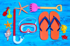 Summer stuff, such as a pair of flip-fllops, a diving mask or a. High-angle shot of a rustic blue wooden table full of summer stuff, such as some starfishes, a Stock Image