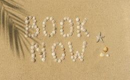 Summer, Sun, Beach - book now. Advertising text BOOK NOW written of snail shells on a sandy beach Stock Images
