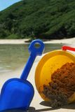 Summer sun - bucket and spade. Image of sandy beach and water with child bucket and spade stock photography