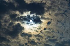 The summer sun hid behind the clouds. Illuminating them from the back side royalty free stock photography