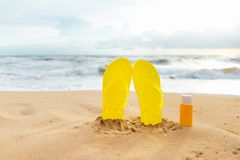 Summer sunbath. Sun lotion bottle in the sand Royalty Free Stock Photo
