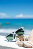 Summer with sunglasses and seashells on the sand Royalty Free Stock Images