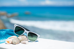 Summer with sunglasses and seashells on the sand. Summer concept with sunglasses and shells on the sand against the blue ocean Stock Photo