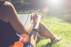 Summer sunny day. Back view. Young woman sits in a park on a lawn and makes notes in a notebook. The girl works, studies Stock Photos