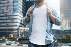 Summer sunny day. Bearded hipster man dressed in white t-shirt,blue denim shirt,stands on city street.Mock up. Royalty Free Stock Photography
