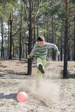 Summer sunny day in the forest boy kicks the ball foot, around a Royalty Free Stock Photo