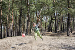 Summer sunny day in the forest boy kicks the ball foot, around a Royalty Free Stock Photos