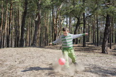 Summer sunny day in the forest boy kicks the ball foot, around a Royalty Free Stock Images