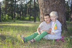 Summer is a sunny day little happy boy and girl are sitting unde Royalty Free Stock Photos